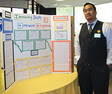 A research student in front of his poster presentation